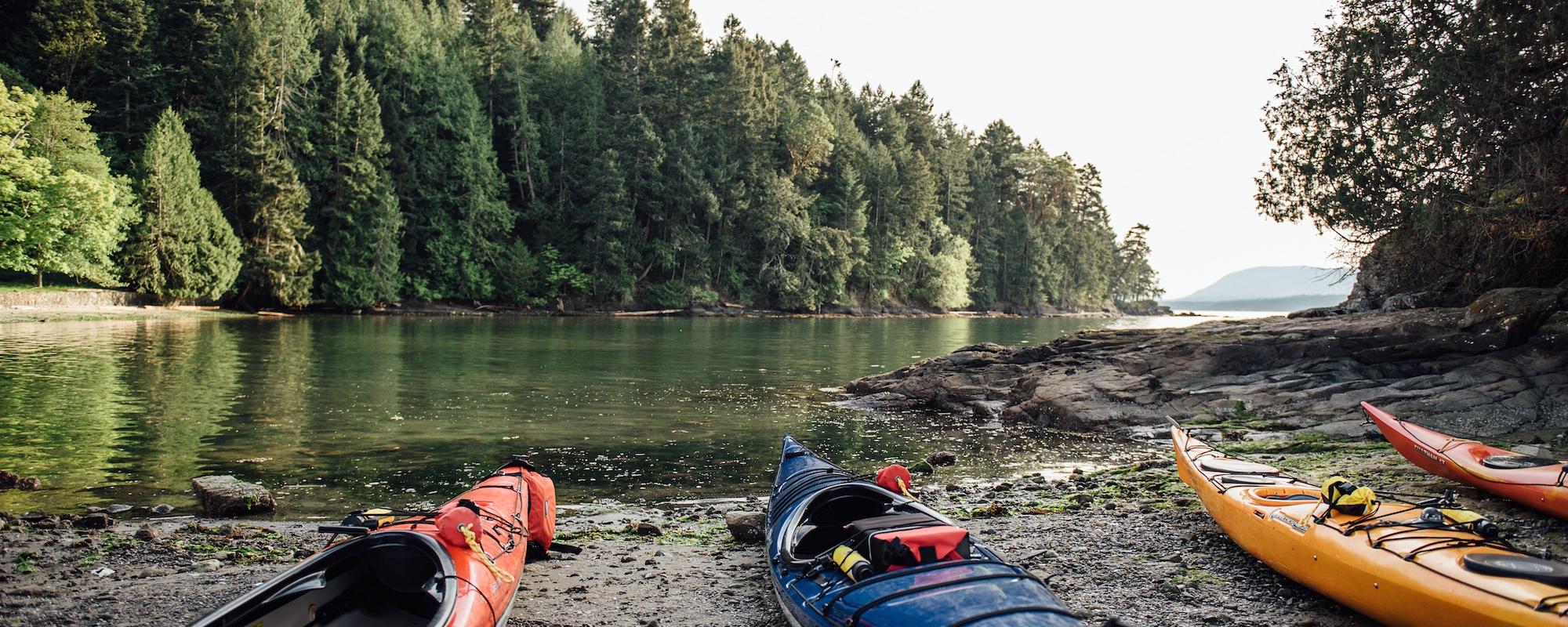 kayaks on the southern gulf islands' shore belonging to  Pender Island Kayak Adventures
