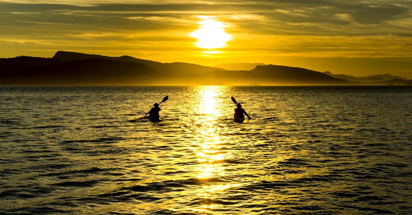 Kayaks paddling into the sunset, Southern Gulf Islands, British Columbia